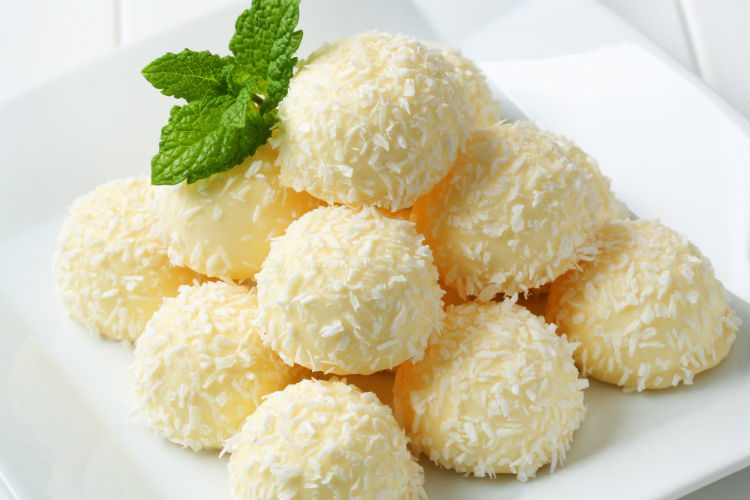 A pile of white chocolate truffles rolled in dessicated coconut,with a sprig of mint leaves on top