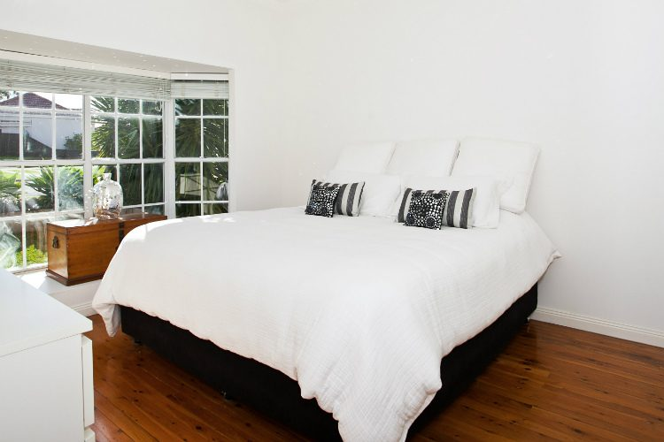 A modern white bedroom with dark hardwood floor - picking the right decor can help you to create the mood you want in your home