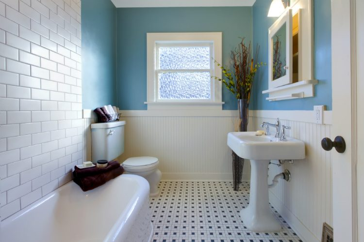 A vintage style blue/green bathroom with white bathroom furniture and black and white tiled floor