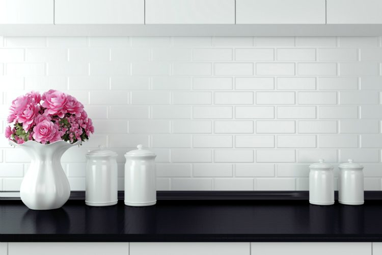 A white kitchen with black worksurface and a white vase containing pink flowers