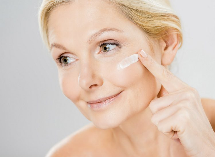 A middle aged woman applies face cream to her face