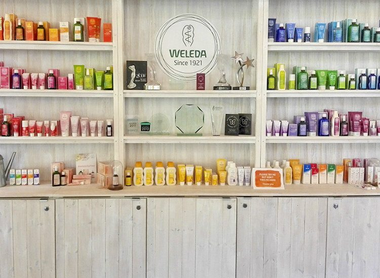 Light wood shelves holding a wide selection of Weleda natural beauty products