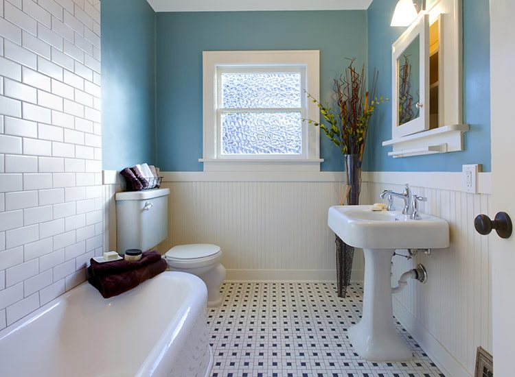 A vintage style bathroom with blue walls, white bathroom suite and tiles