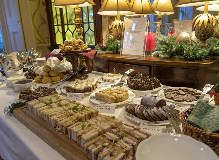 Afternoon tea at at Gliffaes Country House Hotel, which is served buffet style from a table at one end of the sitting room. Plates of sandwiches, scones and cakes are arranged on a large table covered with a white tablecloth