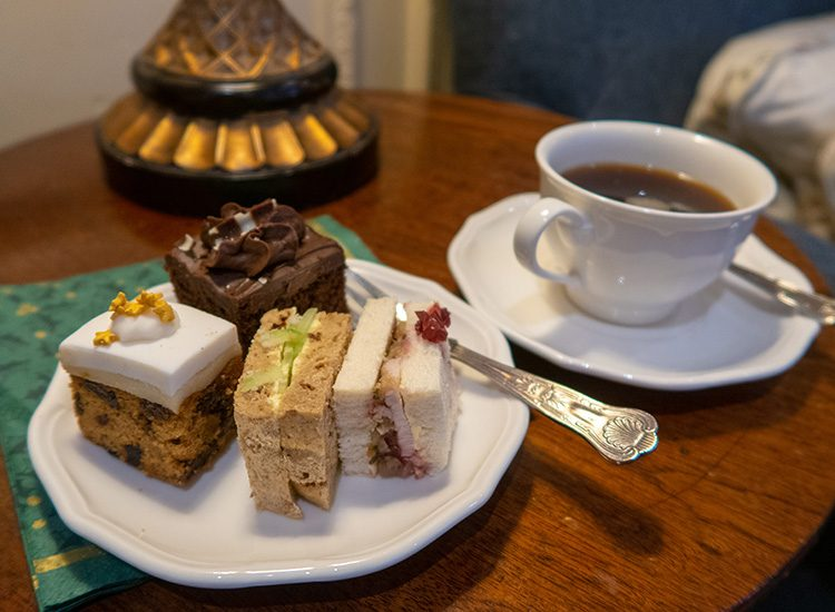 Afternoon tea at Gliffaes Country House Hotel. A small white china plate sits on a wooden table with a selection of cakes and sandwiches. A white china cup of black coffee sits alongside
