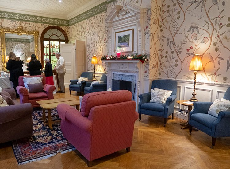 The sitting room at Gliffaes Country House Hotel. with berry coloured sofas and armchairs arranged around a white fireplace