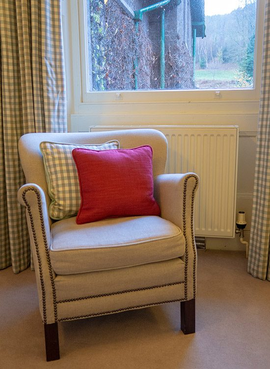 A cosy armchair in the window of a Classic double room at Gliffaes Country House Hotel in Wales