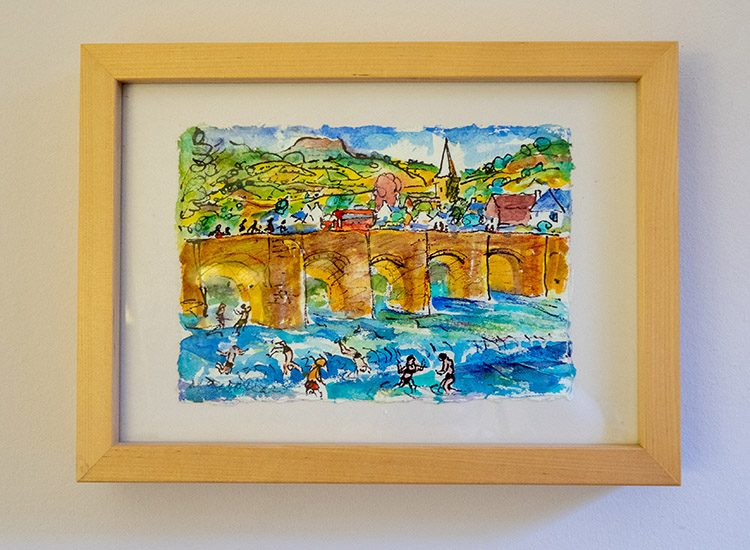 A painting of Crickhowell Bridge hanging on the wall at Gliffaes Country House Hotel near Brecon in Wales