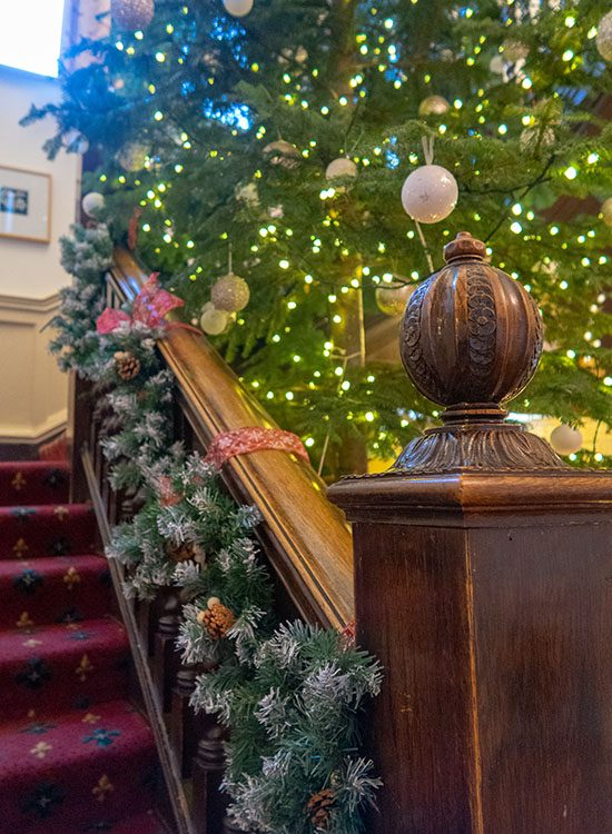 An ornate wooden bannister at Gliffaes Country House Hotel. It is decorated with a Christmas garland, and a Christmas tree with fairy lights is in the background.