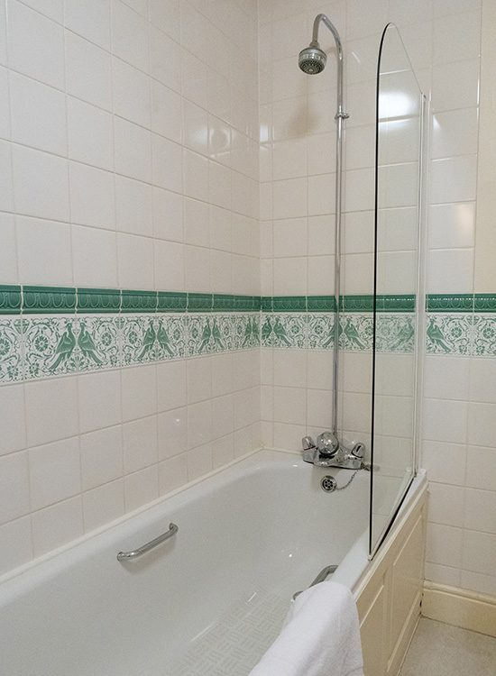 The ensuite bathroom at Gliffaes Country House Hotel with a shower over a white bath and white and green tiles