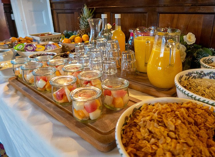 The continental buffet at Gliffaes Country House Hotel. Large bowls of cereals sit next to large jugs of fresh orange juice and glasse. There are glass pots of fresh fruit salad sitting at the front of the table
