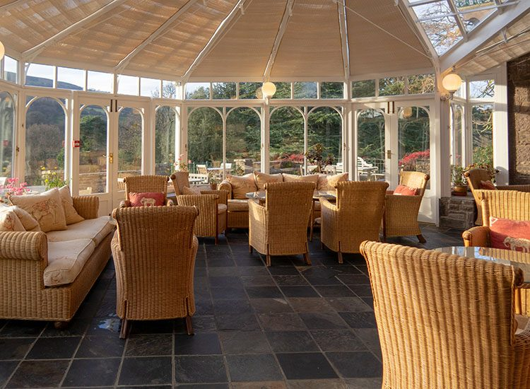 Inside the conservatory at Gliffaes Country House Hotel. Tables are dotted around, with wicker armchaiirs and sofas around them