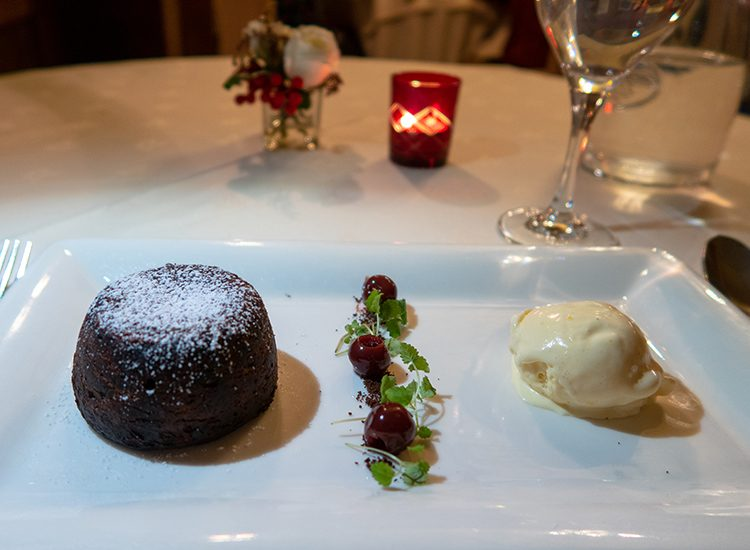 Pudding at Gliffaes Country House Hotel. A chocolate fondant sits on the left hand side of a rectangular white china plate. A scoop of vanilla icecream sits on the right hand side of the plate, and in between is a line of three cherries and grated chocolate