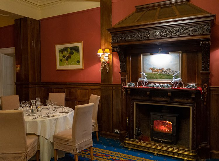 Inside the dining room at Gliffaes Country House hotel. A round table is covered with a white tablecloth, and surrounded by chairs. The walls are painted in a rich red colour and there is wood panelling on the lower half of the walls. A fire burns in the grate of an elaborate wood fireplace, and there are silver Christmas decorations on the mantelpiece