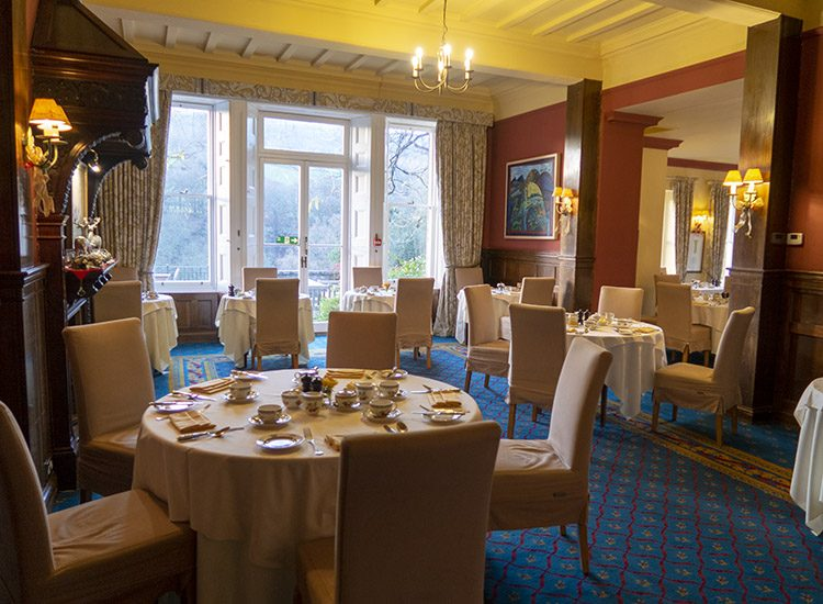 The dining room at Gliffaes Country House Hotel, set up for breakfast. Tables are covered with white tablecloths, and the curtains have been opened to reveal large windows looking out into the gardens