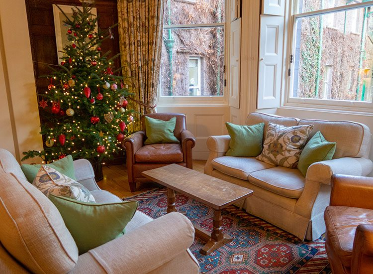 A cosy corner in the bay window of the  drawing room at Gliffaes Country House Hotel. Two cream coloured sofas sit opposite each other, and there are plenty of plump cushions on each. There's a Christmas tree in the corner, which is decorated with lights and baubles