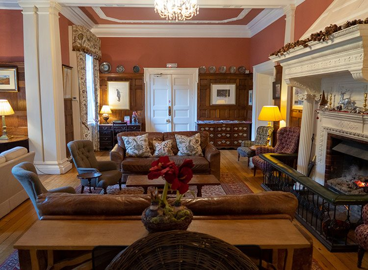 The drawing room at Gliffaes Country House Hotel is decorated with red walls and white pillars and cornices. The fire is glowing red in the fireplace and there are comfy leather sofas