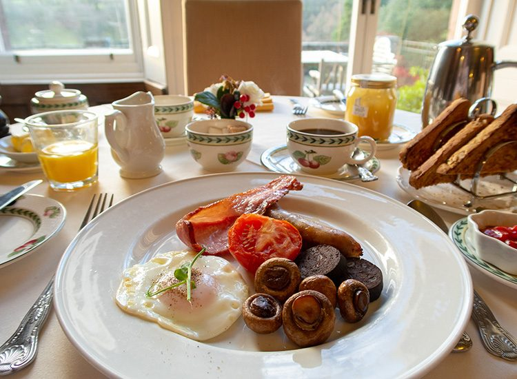 A full Welsh breakfast at Gliffaes Country House Hotel. A round white china plate carries sausage, bacon, black pudding, mushrooms, tomato and a fried egg. In the background there is a glass of orange juice, a cup of black coffee and a toast rack with a large jar of honey