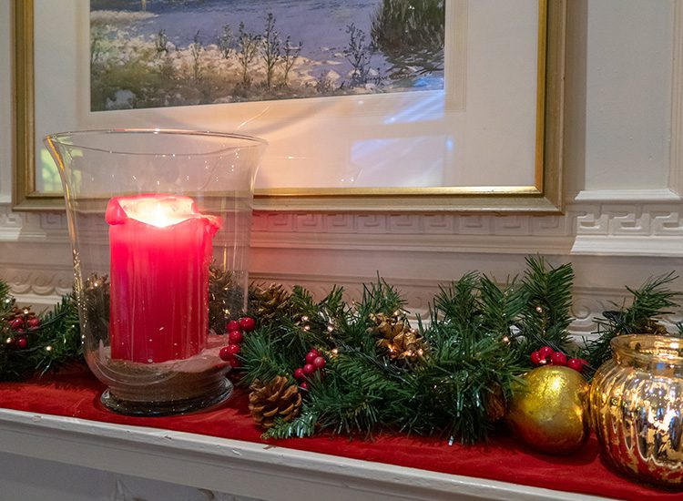 Close up of a large red candle in a glass jar and a Christmas garland on a mantelpiece at Gliffaes Country House Hotel.