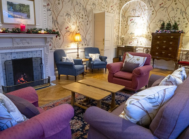 The sitting room at Gliffaes Country House Hotel. There is a floral patterned wallpaper on the walls, and comfortable sofas and armchairs in rich berry colours. A fire glows in the fireplace, which is decorated with a large red candle and a Christmas garland