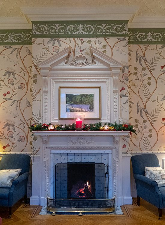 An ornate white fireplace in the sitting room at Gliffaes Country House Hotel. A fire burns in the grate, and there are candles and a garland on the mantelpiece