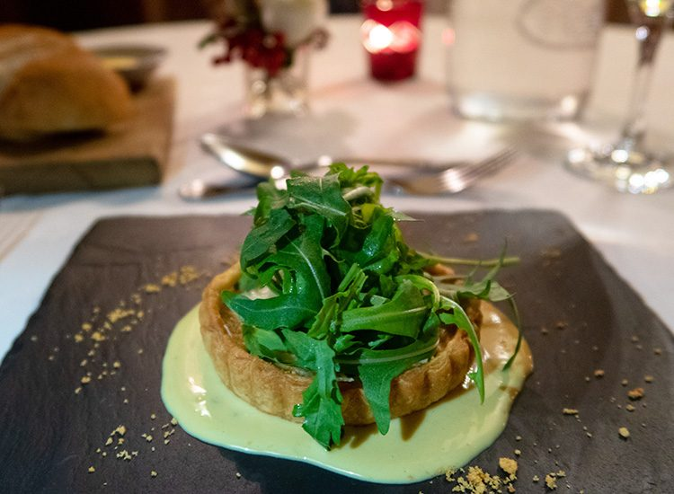 Starter at Gliffaes Country House Hotel. A Crab and Welsh Ale tartlet sits on a square slate plate. It is topped with Welsh Rarebit and Breconshire rocket.