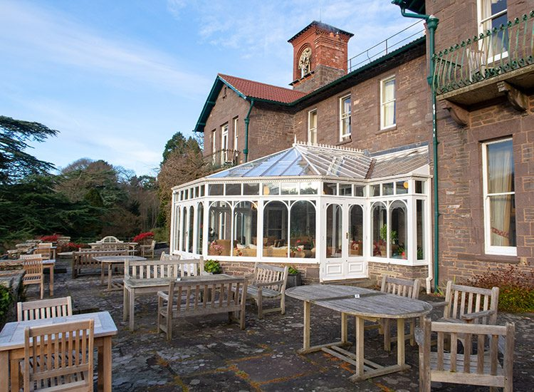 The terrace behind Gliffaes Country House Hotel. The hotel's conservatory can be seen, and there are several tables and chairs on the terrace