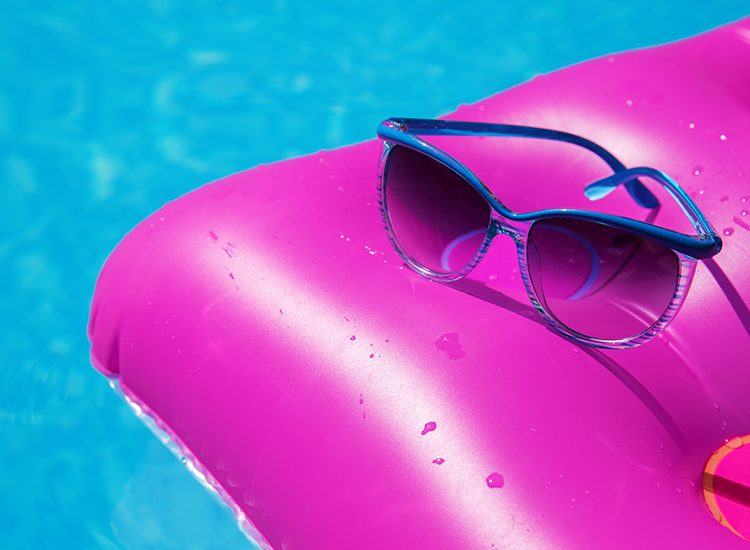 A bright pink pool lilo floats on the clear blue water of a swimming pool. There's a pair of blue sunglasses resting on top of the lilo