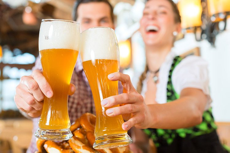 A man and a woman smile and clink together traditional German glasses of beer