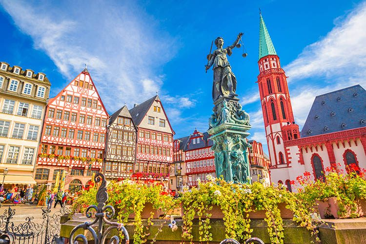 The traditional old architecture of Frankfurt-am-Main - colourful houses, a red and white church and a large statue surrounded by flowers