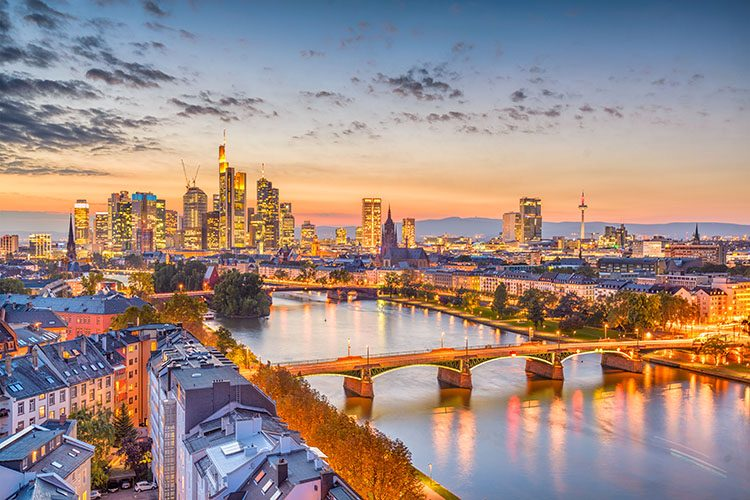 The skyline of Frankfurt-am-Main, Germany, lit up at night. The river runs through the centre of the city and the sun is setting in the distance