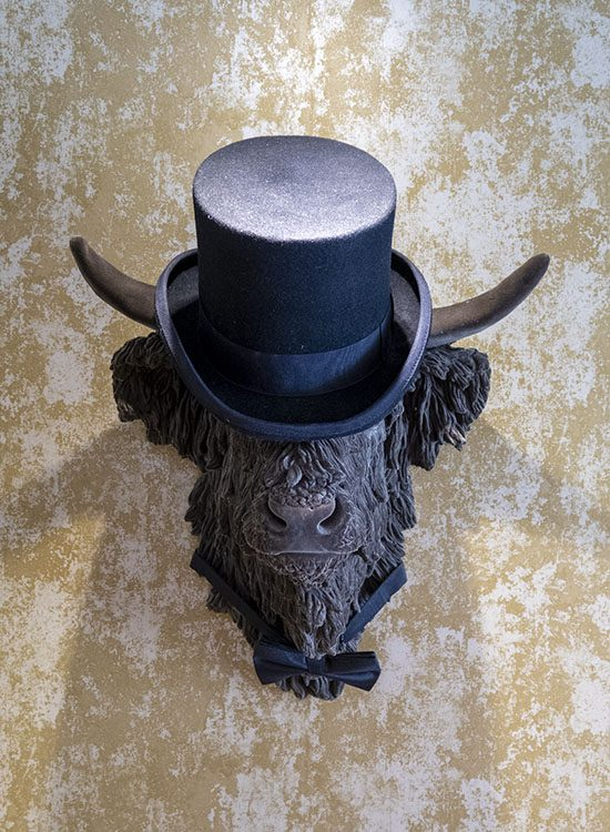 An ornamental head of a bull, wearing a black top hat