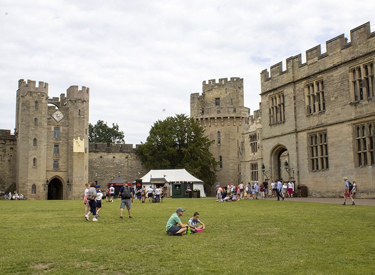 A view of the courtyard at Warwick Castle in Warwickshire UK, showing the gatehouse and Caesar's Tower. People are milling around and some are taking a rest on the grass
