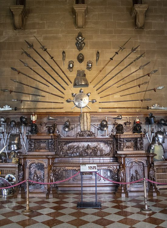 The Kenilworth Buffet, an intricately carved wooden sideboard on show in the Great Hall at Warwick Castle in Warwickshire UK. An array of weaponry hangs on the wall above.