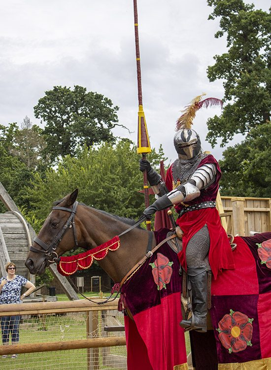 An actor dressed in armour and carrying a jousting staff sits on a dark brown horse in the Wars of the Roses show at Warwick Castle, Warwickshire, UK. They are both wearing the red colours of the House of Lancaster