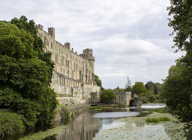 A view of Warwick Castle in Warwickshire, UK, showing the wall that backs onto the River Avon. The river flows through the middle of the image and there are trees to either side
