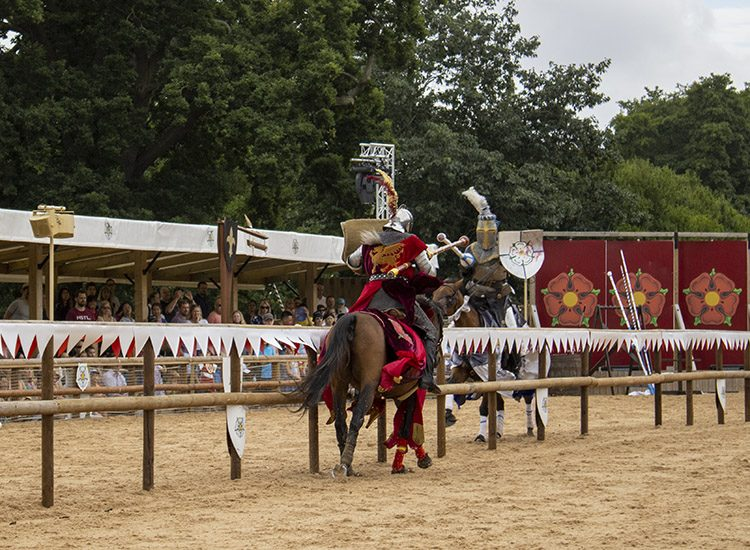 Two jousting knights on horses in the Wars of the Roses Live show at Warwick Castle in Warwickshire UK. A crowd looks on, and there are banners displaying the red rose of the House of Lancaster in the background