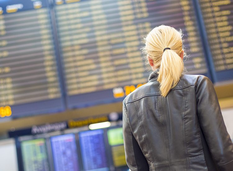 A woman looks up at the departure board at the airport