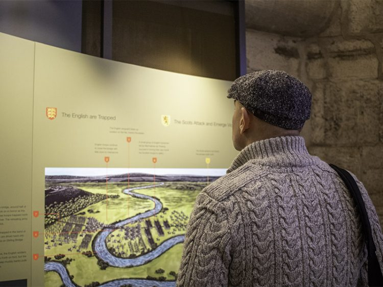 A man stands looking at the display in the Royal Chamber of the National Wallace Monument, with information about the Battle of Stirling Bridge