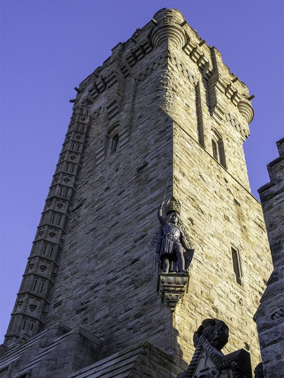 A view looking up at the National Wallace Monument, showing the sculpture of William Wallace holding his sword in the air