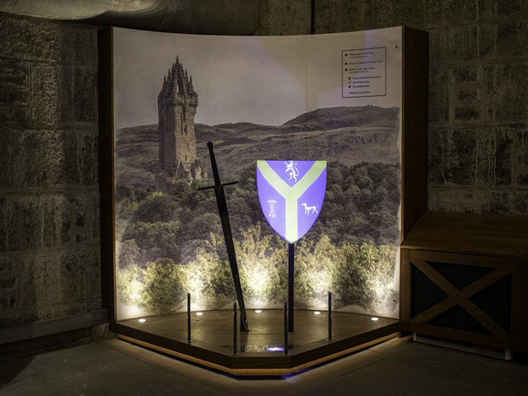 A coat of arms is projected onto a shield, with a sword next to it. They are both standing in front of a large image of the National Wallace Monument