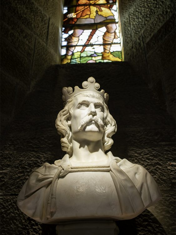 A marble bust of King Robert the Bruce inside the Hall of Heroes at the National Wallace Monument. Behind the bust is a stained glass window depicting a spearman ready for battle