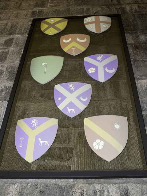 A collection of coats of arms are projected onto shields hanging on the wall of the National Wallace Monument