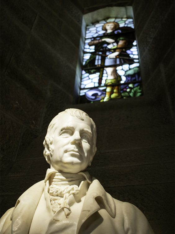 A marble bust of Sir Walter Scott inside the Hall of Heroes at the National Wallace Monument. Behind the bust is a stained glass window depicting an archer ready for battle