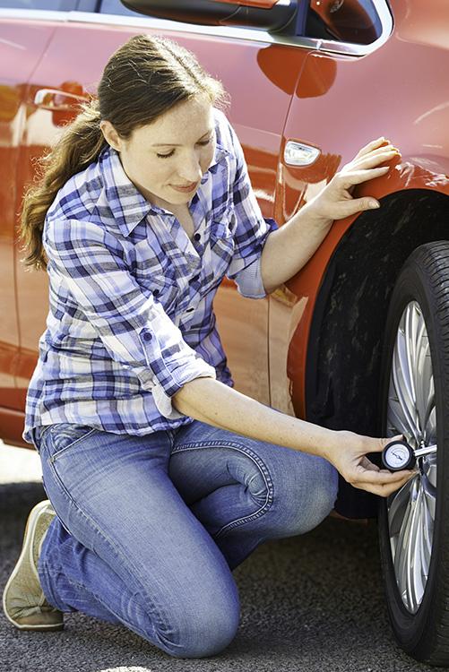 Woman Checking Car Tyre Pressure Using Gauge