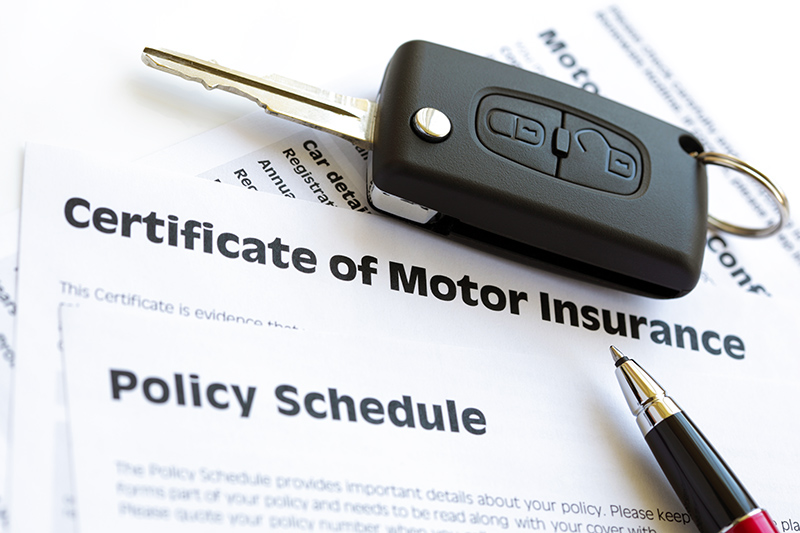 A Motor Insurance certificate with car keys and a pen