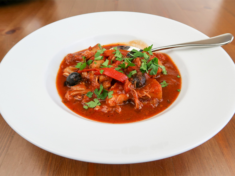 A white bowl filled with chicken cacciatore from the slow cooker