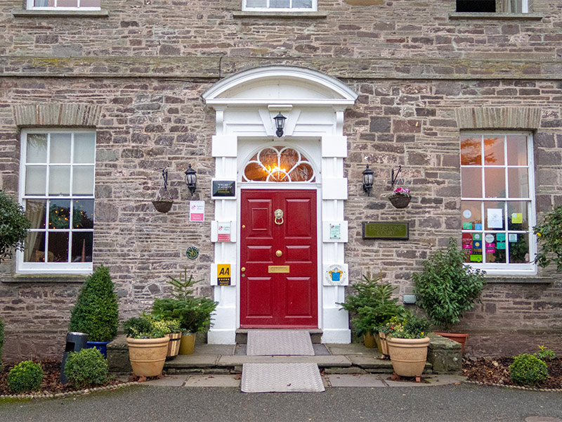 The red front door of Peterstone Court Hotel near Brecon in South Wales, UK