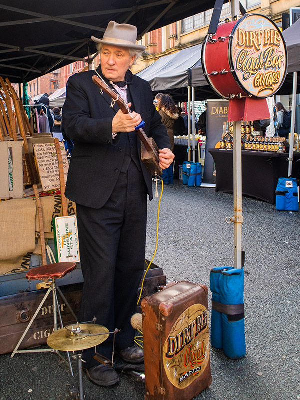 A man plays a cigar box guitar at the Makers Market in the Northern Quarter, Manchester, UK
