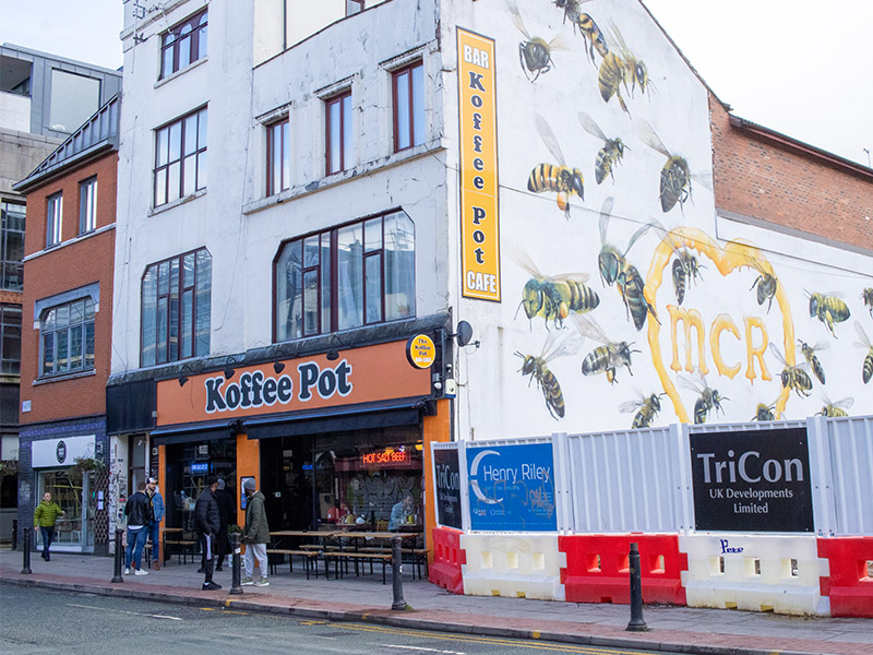 The Koffee Pot diner in the Northern Quarter, Manchester, UK, showing the street art of bees on the side of the building